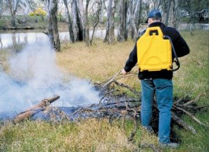Fire fighting knapsack putting out bushfire on farm